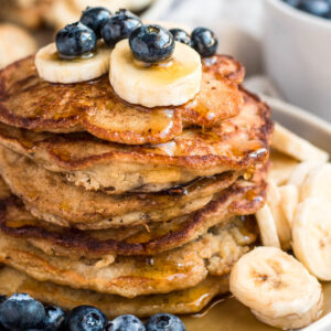a stack of banana oat pancakes with bananas and blueberries on top