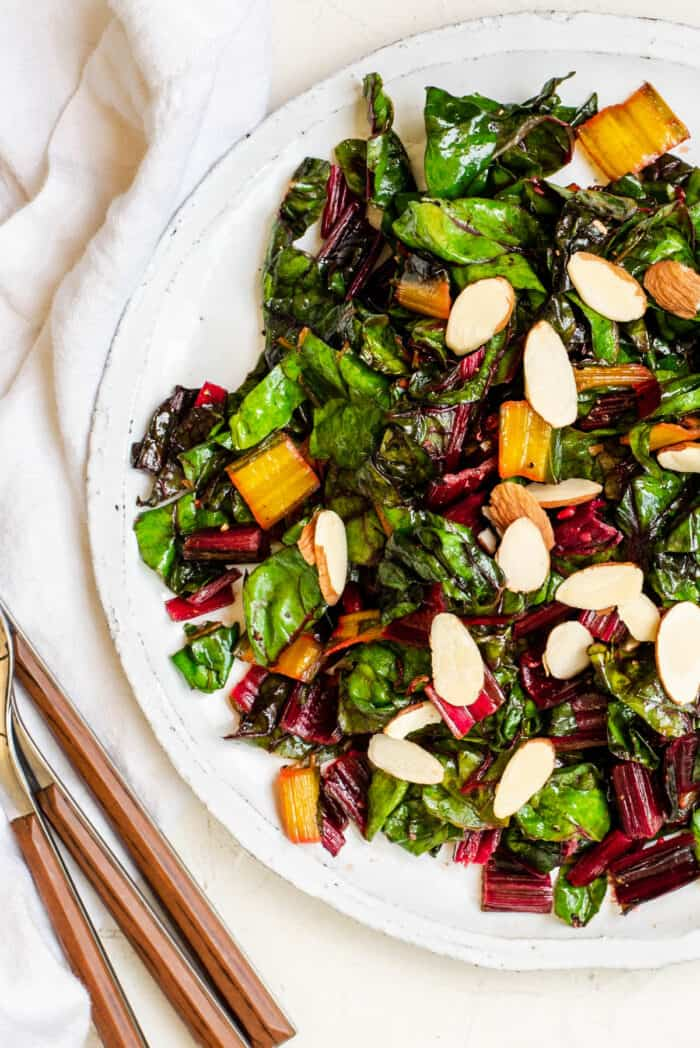 sauteed rainbow chard on a plate with sliced almonds on top