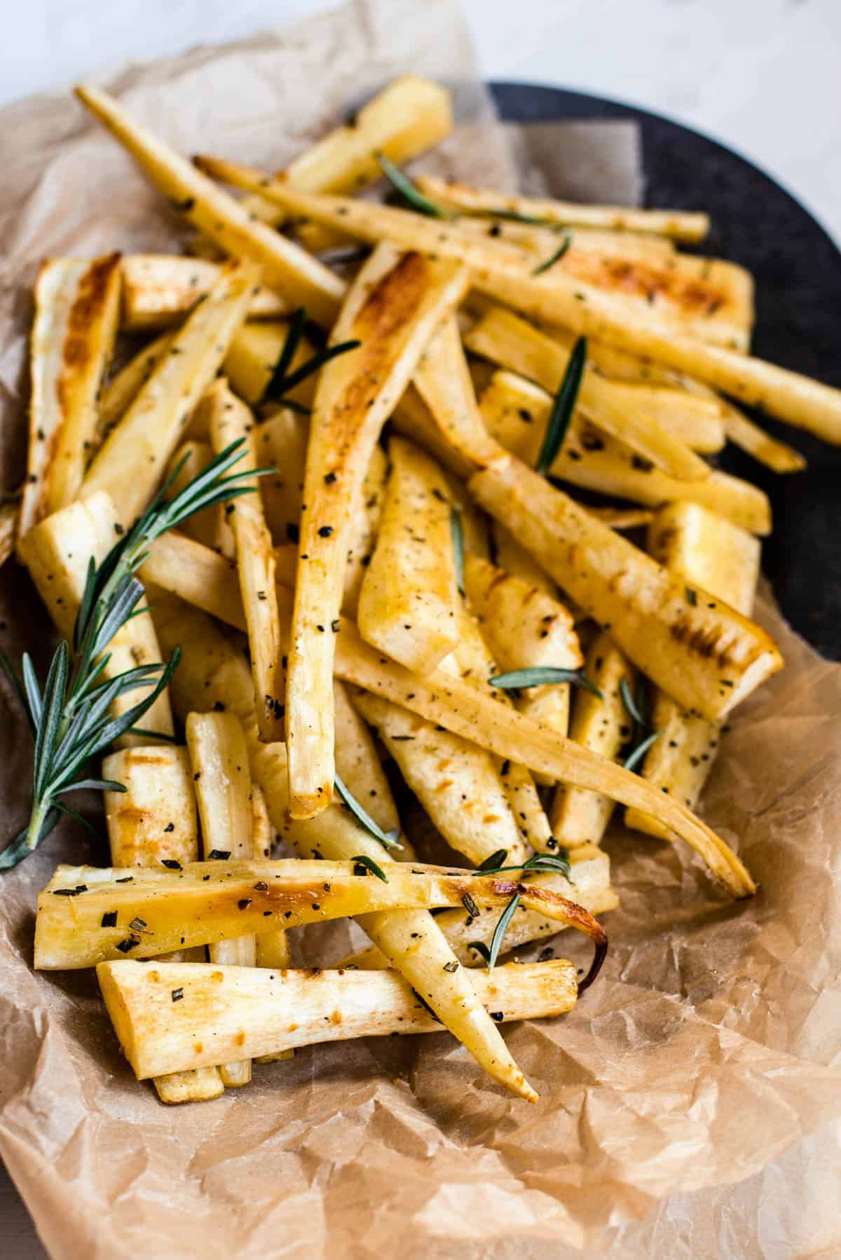 baked parsnips in a serving dish with a sprig of parsley