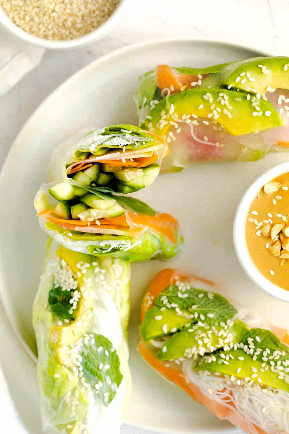 a sliced summer roll on a plate with other avocado spring rolls
