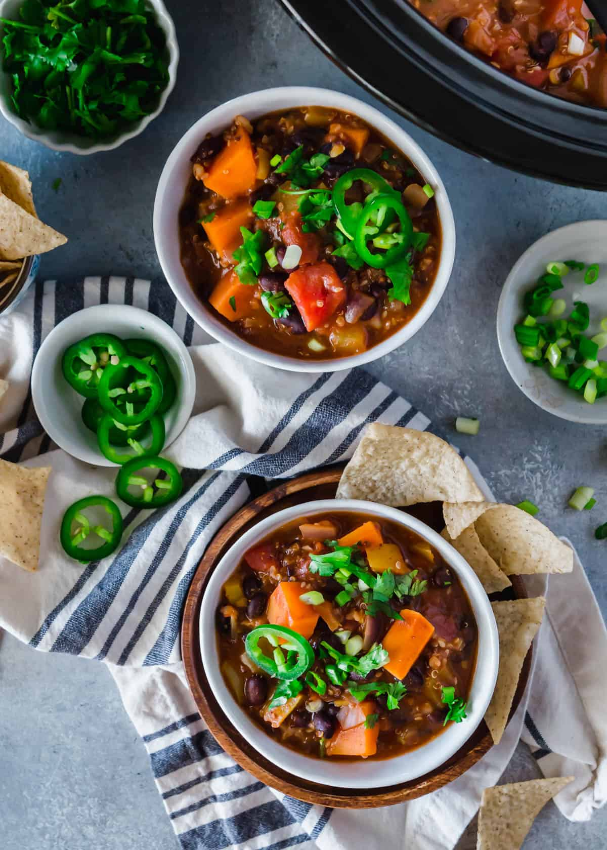 two bowls of sweet potato and quinoa chili on a table with chili garnishes on the side
